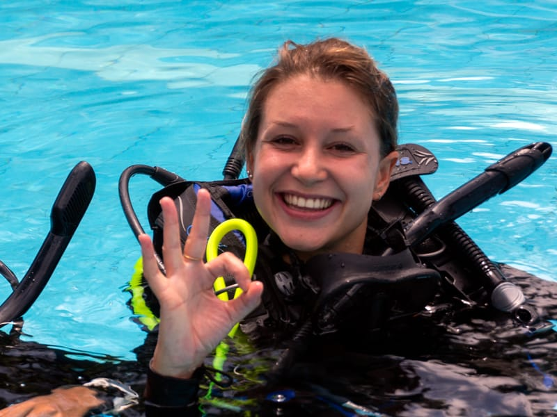 IDC Student in pool giving ok signal