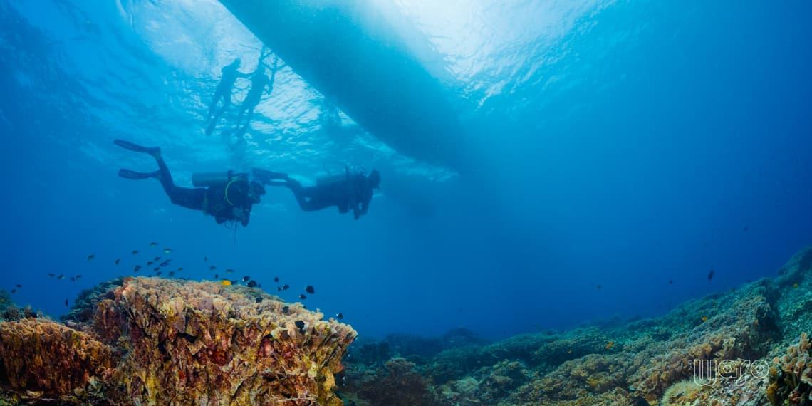 Divers hanging under a boat at Bunaken